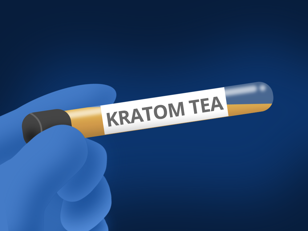 A blue gloved hand holding a test tube containing kratom tea